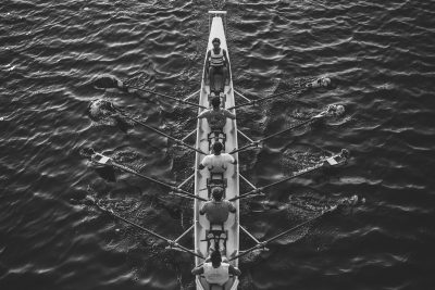 Black and white aerial bird's eye photograph of team rowing in water
