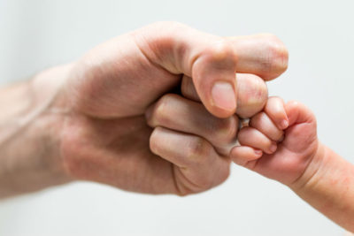NICU parent dad and newborn baby's fists unite for first bump with confidence not hopelessness.