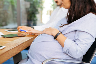 pregnant modern professional woman seated at table during meeting before maternity leave